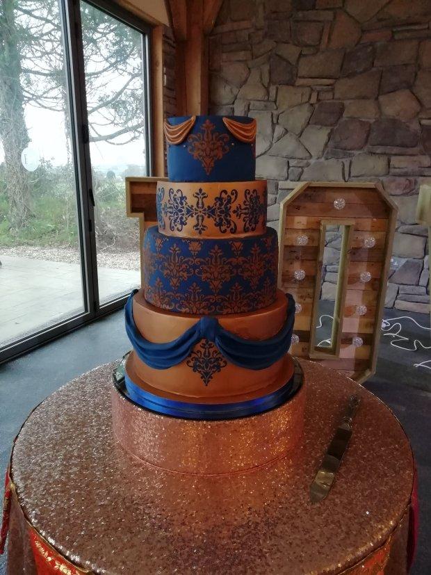 4 tier rose gold & royal blue wedding cake