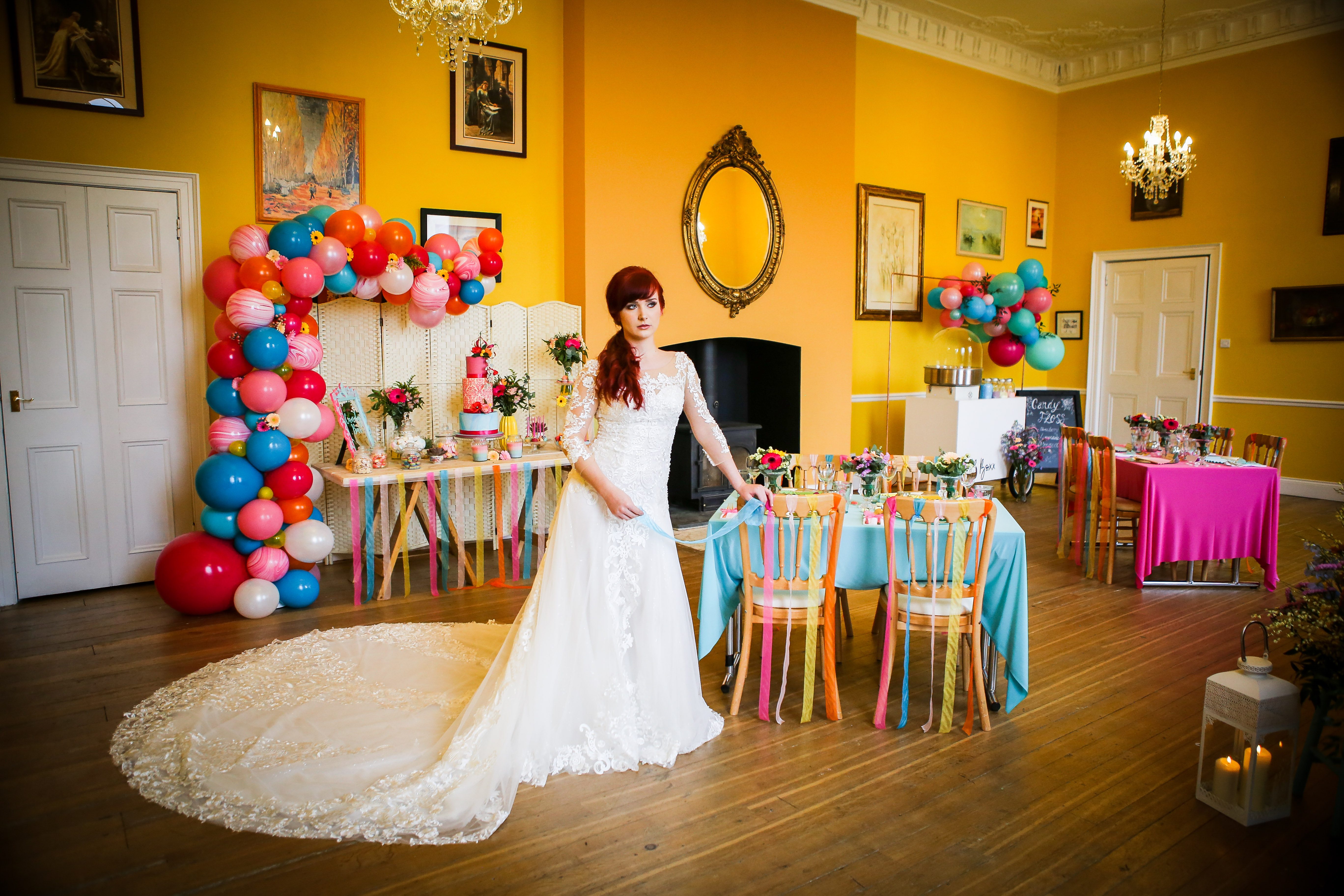 Bride stood by cake table in long train wedding dress
