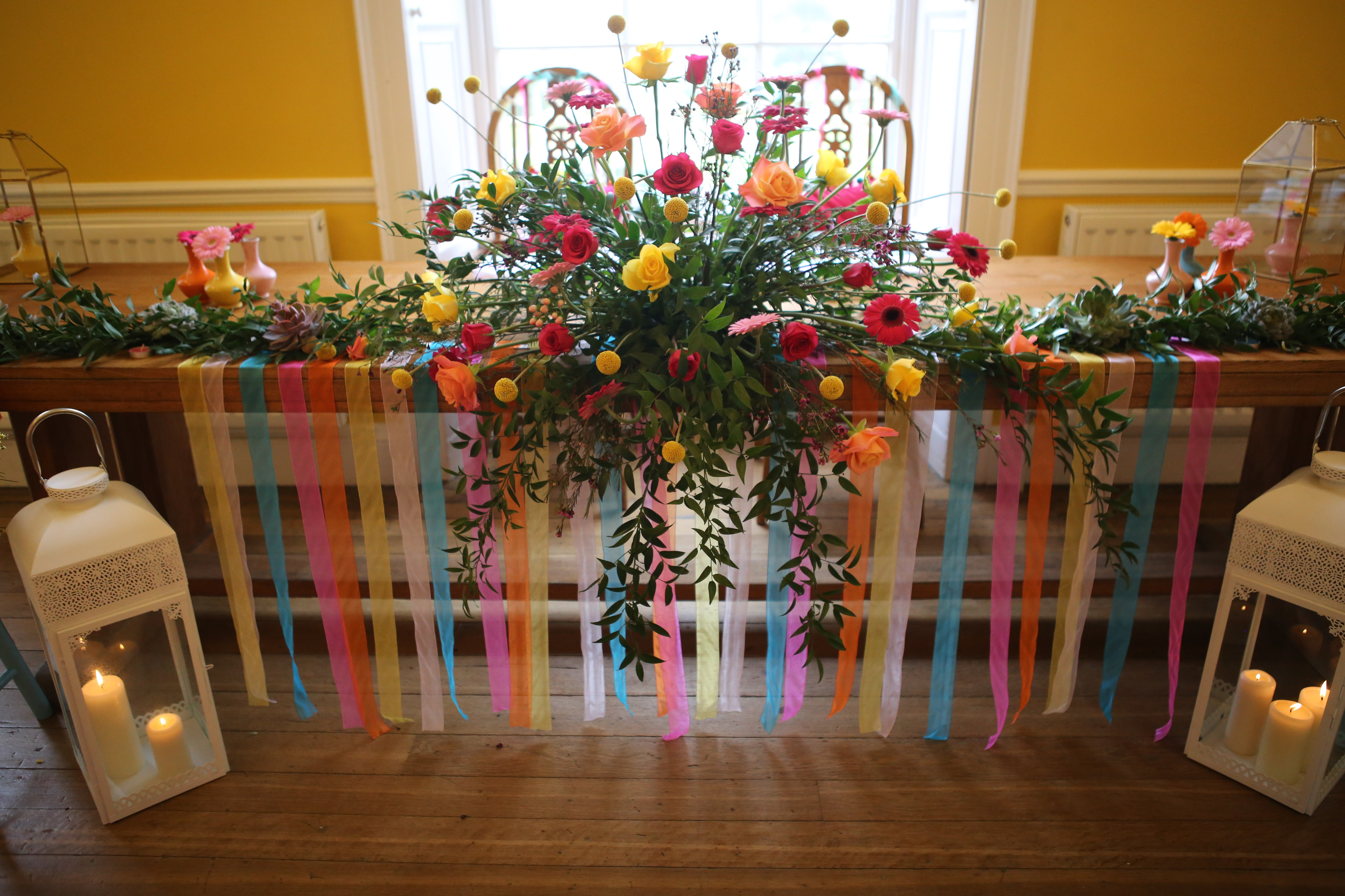 Top table at wedding with flowers and colourful ribbon