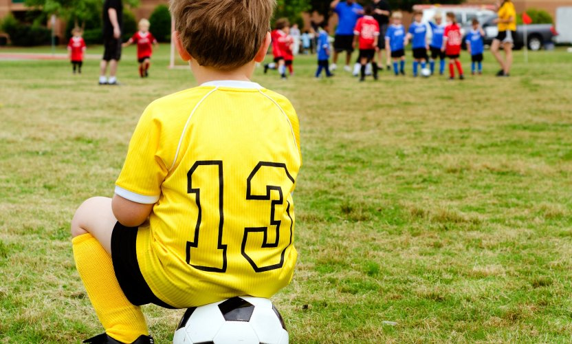 Young boy child in uniform watching organized youth soccer or football game from sidelines; Shutterstock ID 102365713; Purchase Order: -