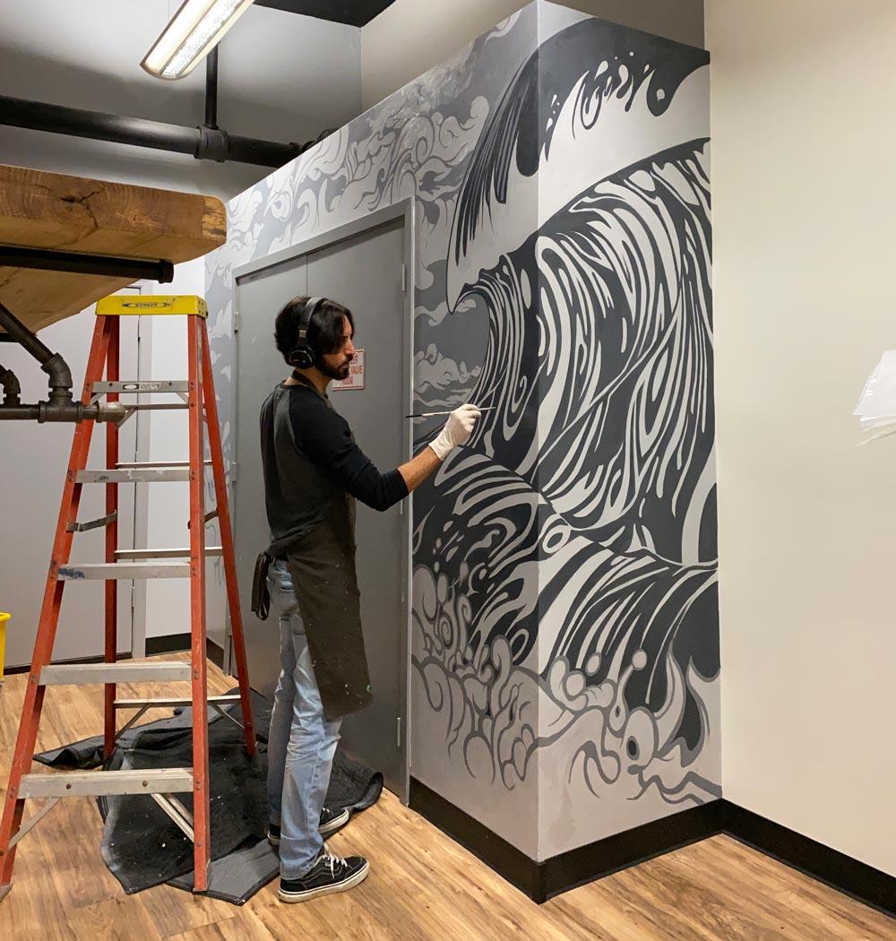 Artist Jay Alders painting an ocean surf theme mural