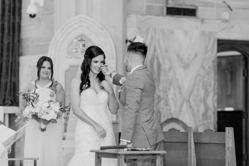 touching moment between bride and groom during religious wedding ceremony, black and white wedding ceremony photo