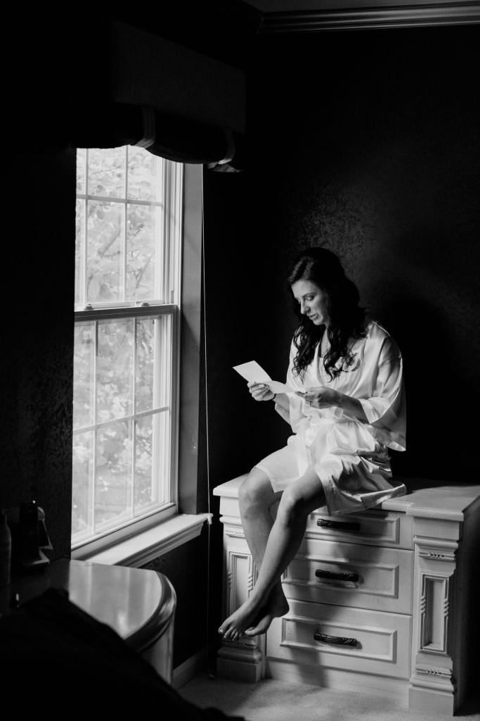 bride getting ready, bride sneaking a private moment to read a letter from her groom black and white photo, bride candid shot