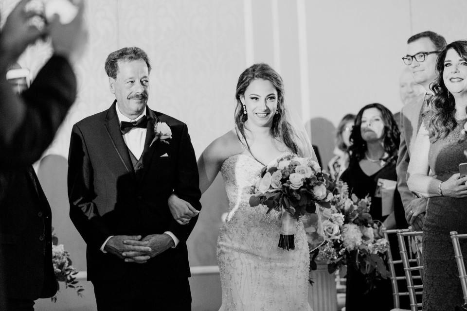 bride walking down the aisle with dad, black and whtie