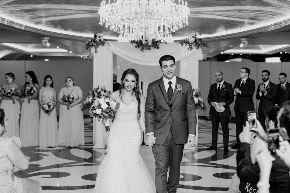 black and white bride and groom walking down the aisle