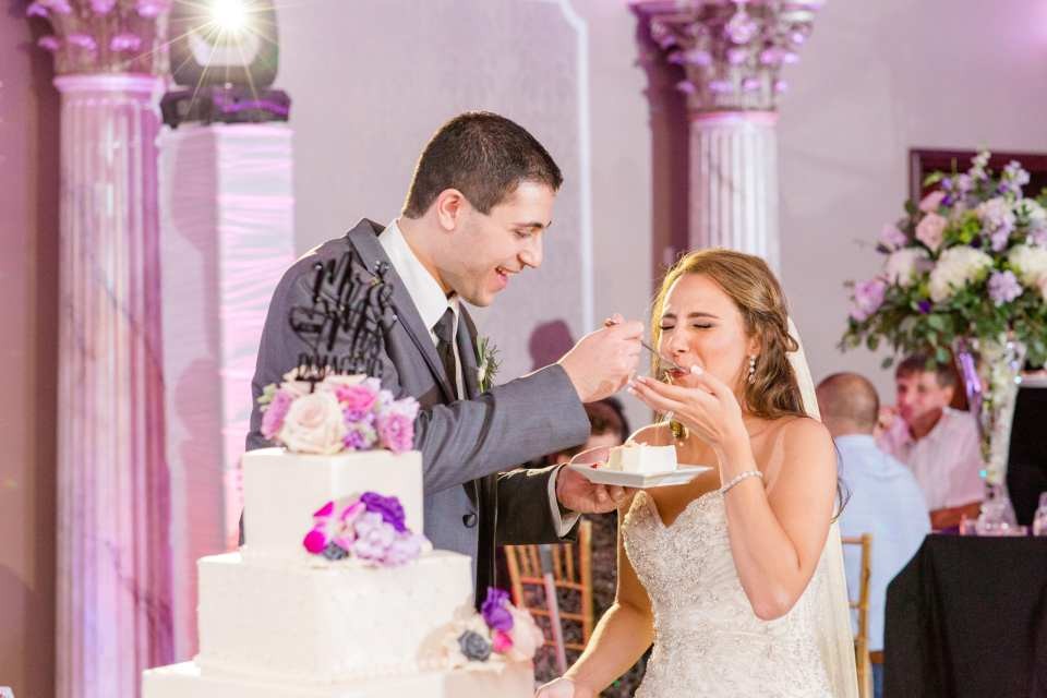 groom feeds bride cake, Grand marquis weddings, classic wedding cake with purple floral decor, Palermo Bakery