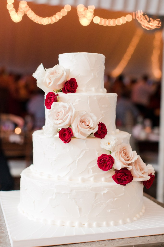 four tier white wedding cake with rose flower garland
