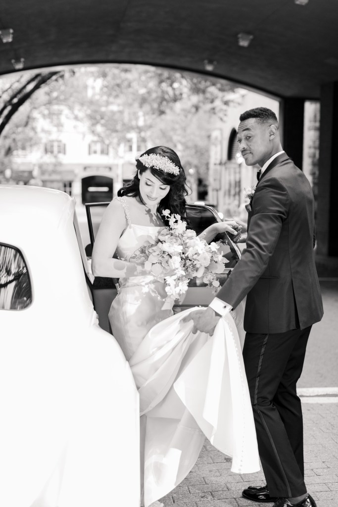 black and white photo of bride and groom, groom helping bride out of car