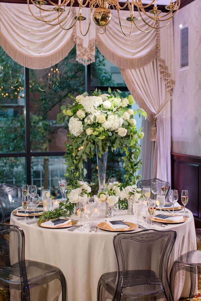 Nassau Inn wedding reception, Princeton NJ indoor wedding reception, tall white rose and hydrangea centerpiece with smaller ones around it, smoke lucite chairs, gold chargers, black menus, NJ wedding photographer