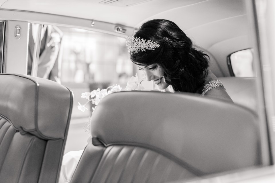 black and white candid of bride in antique car
