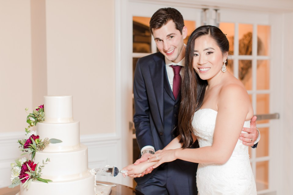 bride and groom classic cake cutting photo, classic white four tiered wedding cake with floral details, bride and groom cut the cake, New Jersey wedding photographer