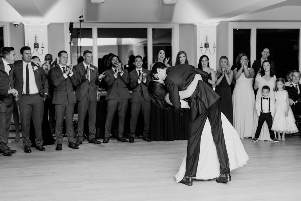 bride and groom first dance at the rock island lake club, groom dips his wife black and white, NJ wedding photographer