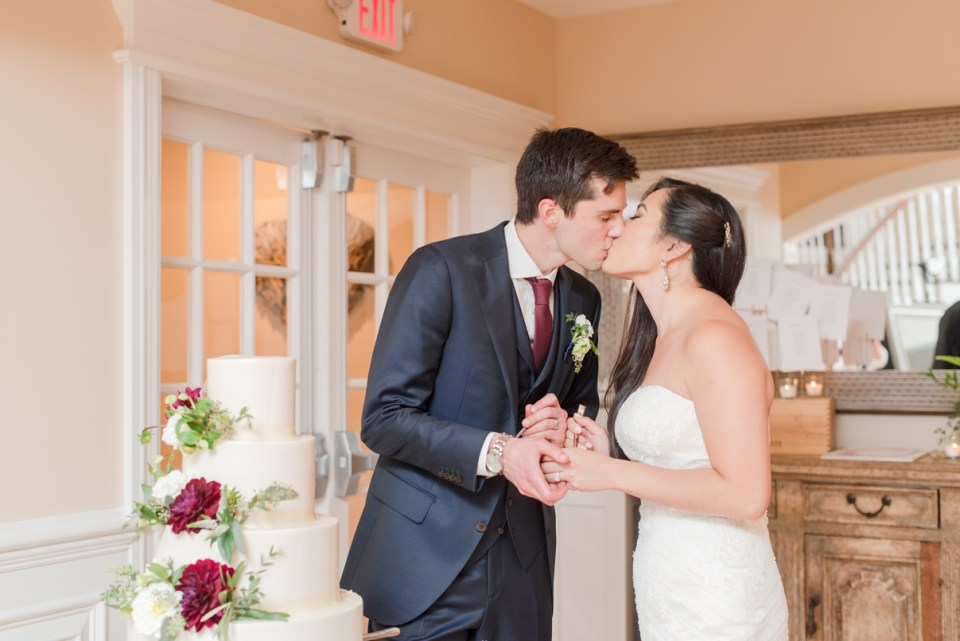 Rustic wedding, bride and groom kissing after cake at rock Island lake club