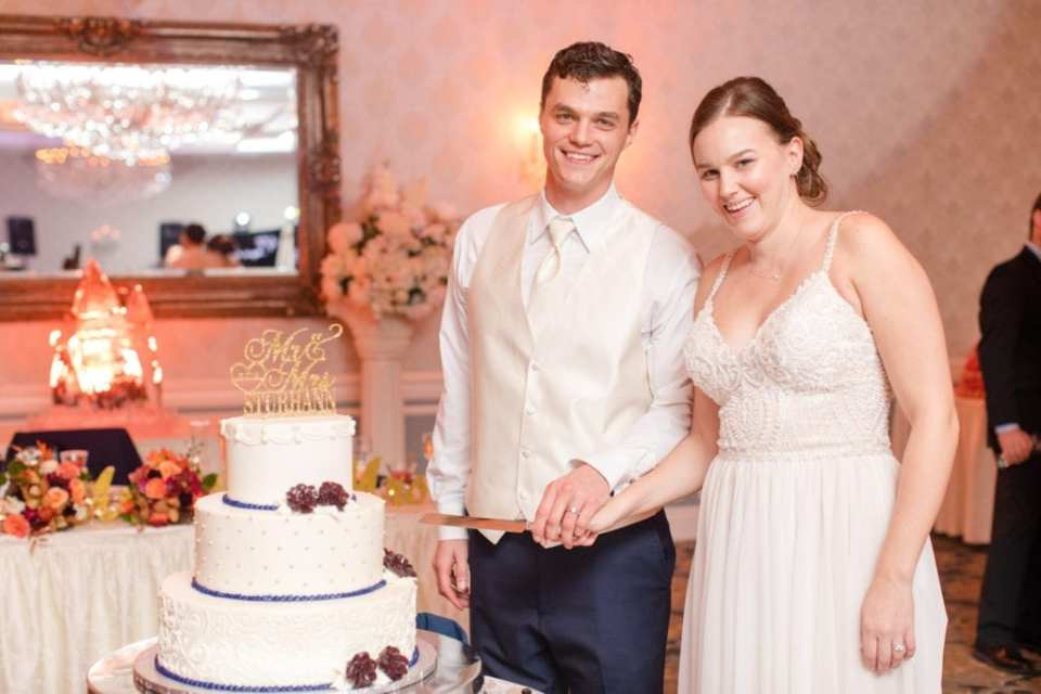 bride and groom taking formal cake cutting photo with cake holding cake cutter