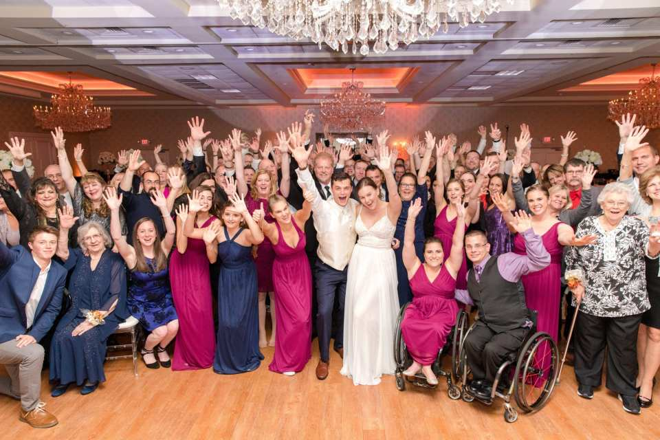 full group photo of bride, groom, wedding party, and all wedding guests