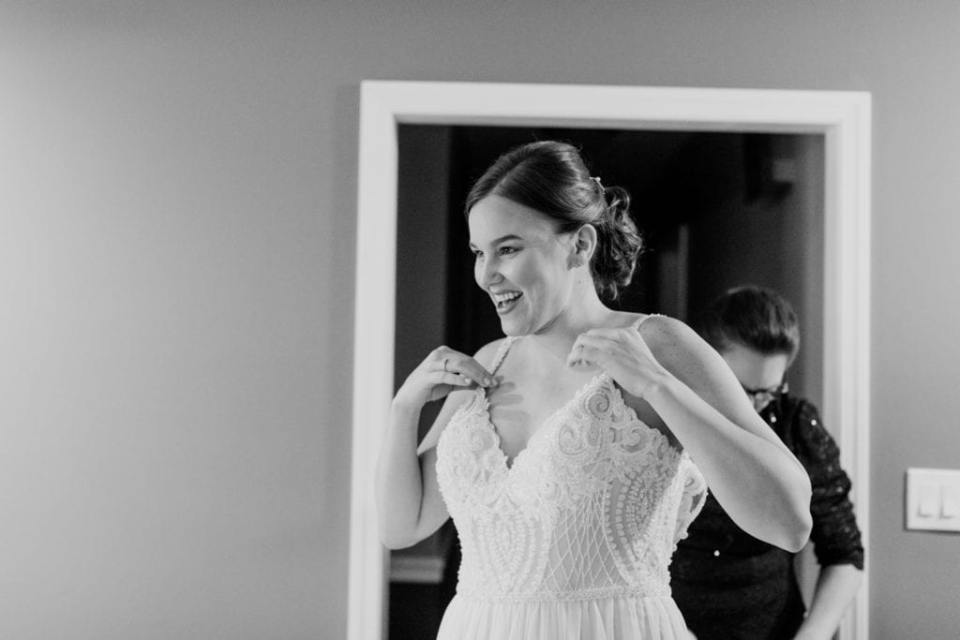 black and white photo of bride getting into her gown
