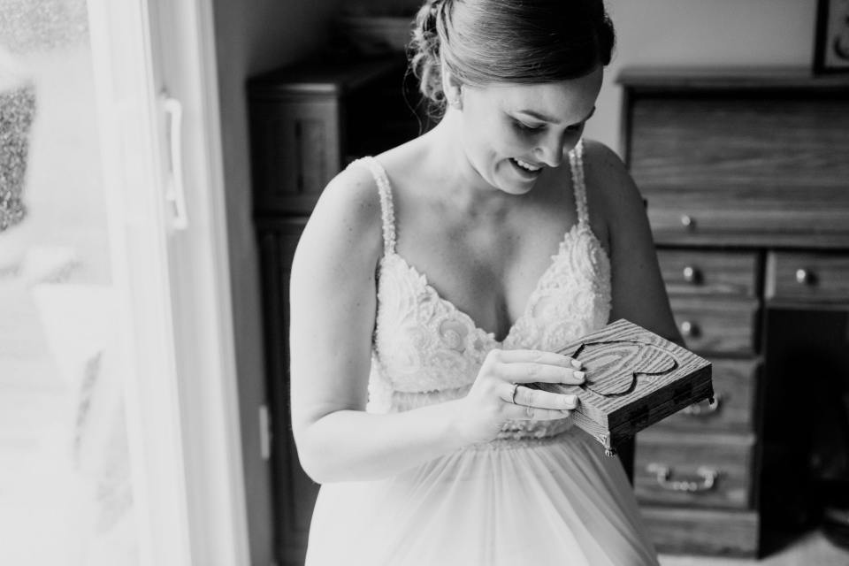 black and white photo of bride smiling while opening a wooden box with a heart carved into it