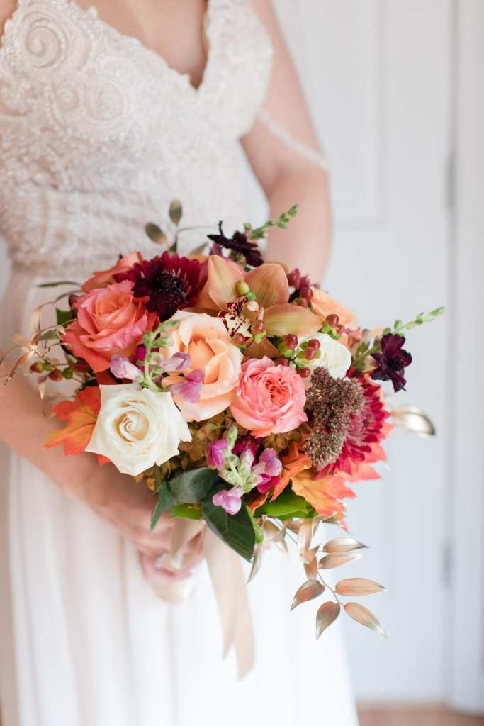 3/4 shot of bride holding her bouquet made up of fall colored roses, dark red asters and fall foliage