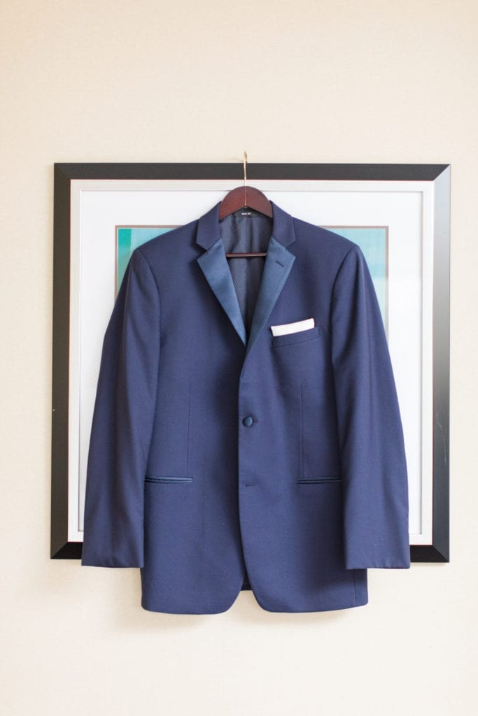 grooms navy blue tuxedo jack displayed against a cream colored wall