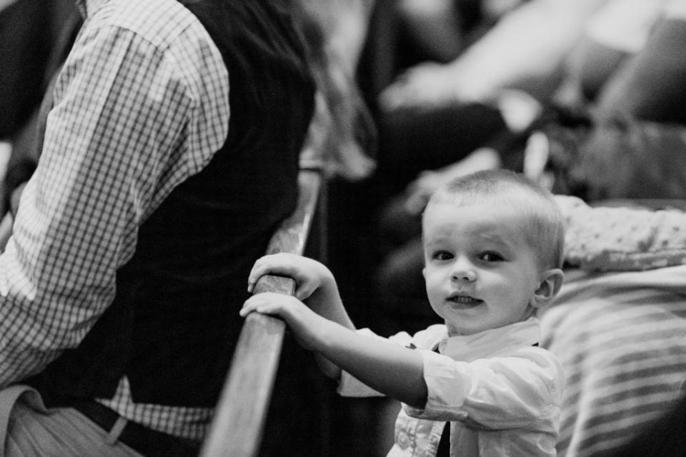 black and white photo of toddler ring bearer looking at camera during church ceremony
