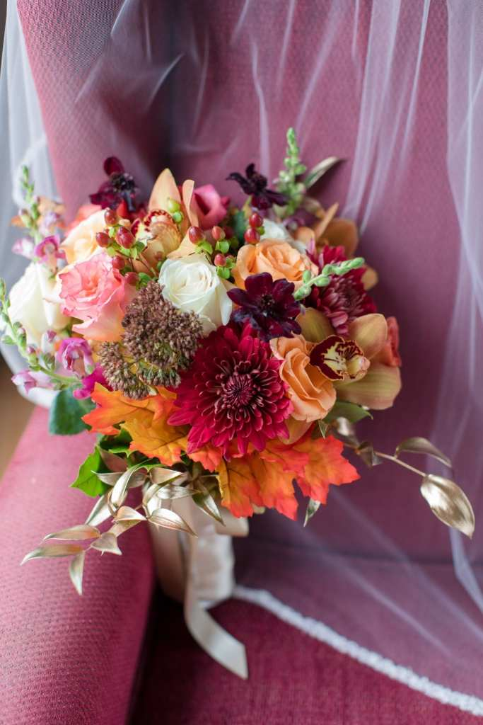 brides bouquet of fall colored flowers: orange, peach, cream colored roses, orange leaves, dark red aster flowers