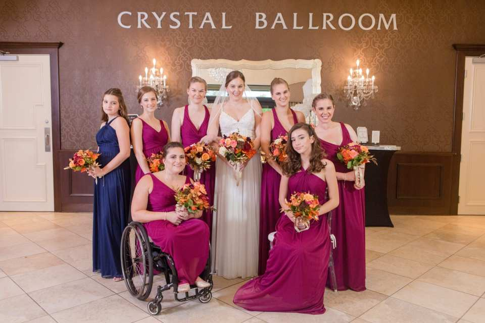 formal bridal party photo with bridal party in raspberry gowns, junior bridesmaid in navy blue gown and bride, all under the Crystal Ballroom sign