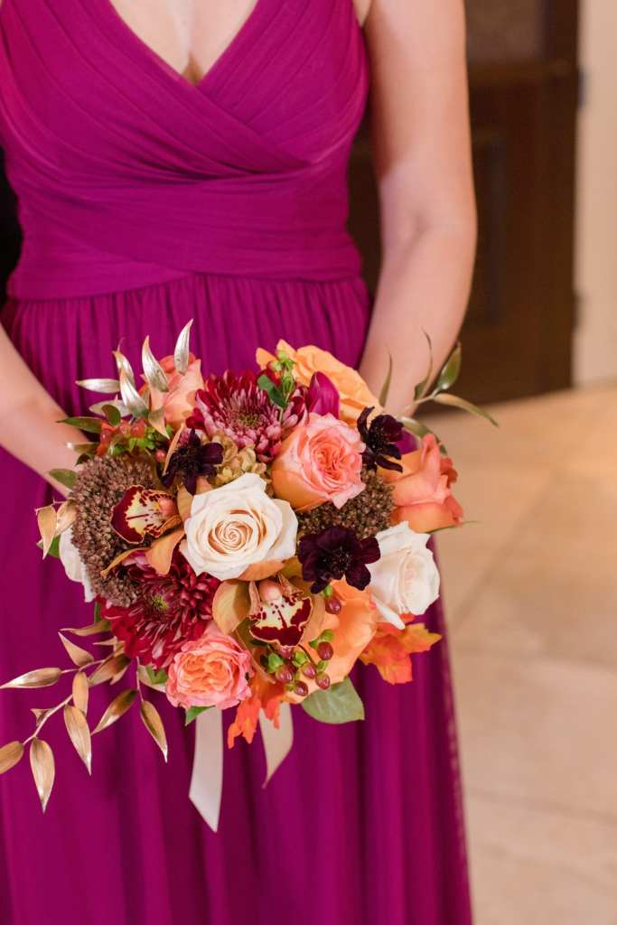 bridal party bouquet of cream and orange roses, fall colored foliage and pinecones help by a member of the bridal party in a raspberry colored gown
