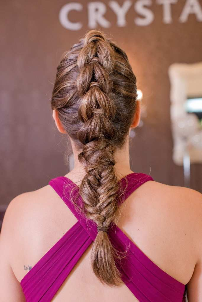 close up of back of bridesmaid hair in raspberry gown