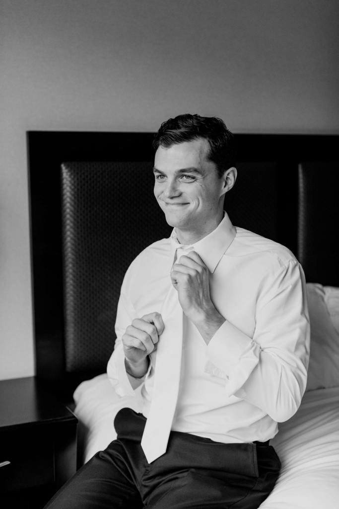 black and white candid photo of groom adjusting his white tie