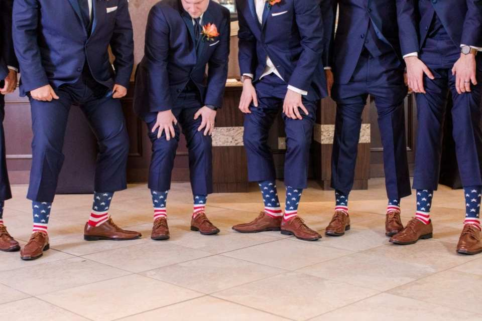 groom and groomsmen showing of american flag socks