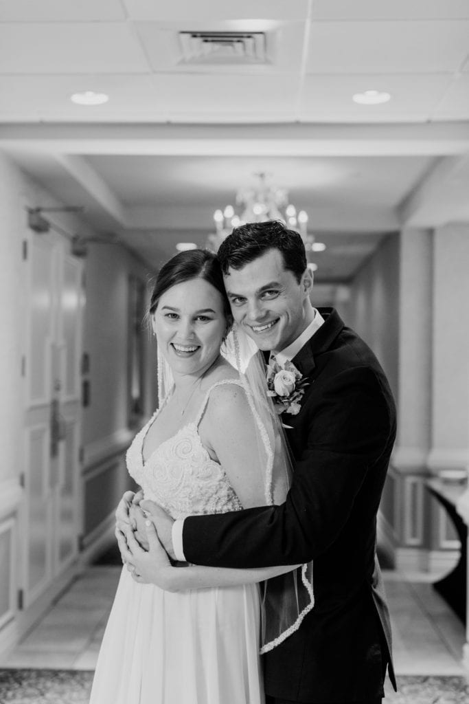 black and white portrait of smiling bride and groom