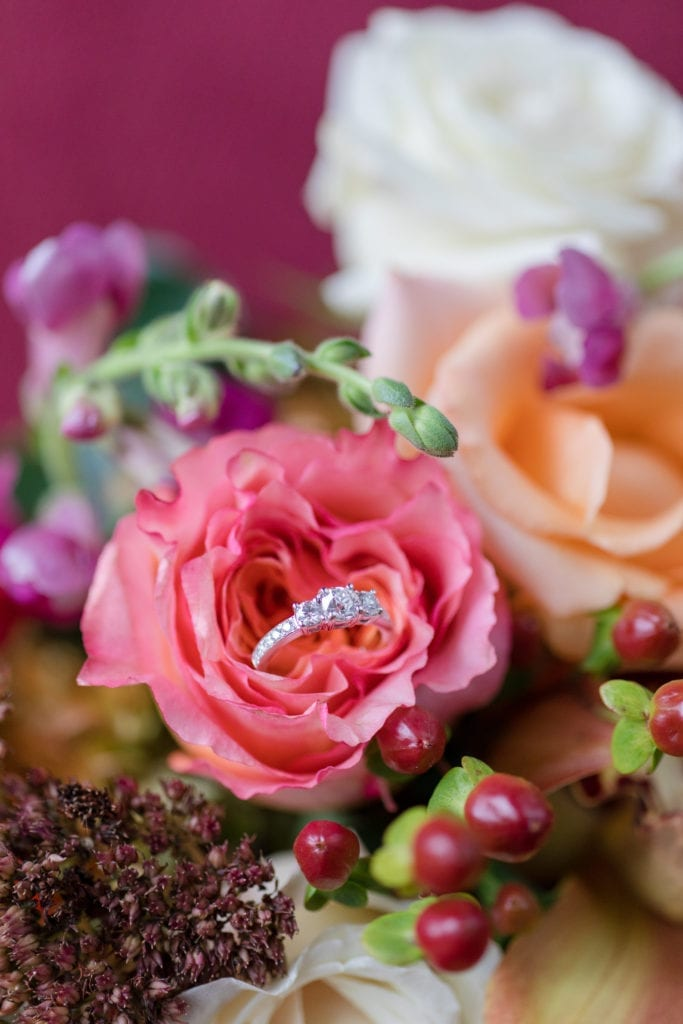 three stone diamond engagement ring with channel set diamonds in a orange colored rose in the brides bouquet