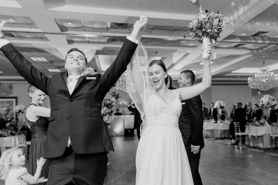 black and white photo of bride and groom celebrating with their arms in the air as they make their entrance into the wedding reception