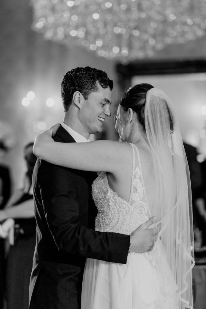 black and white photo of groom smiling at bride during their first dance