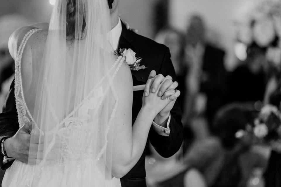 close up black and white photo of father holding brides hand during father daughter dance