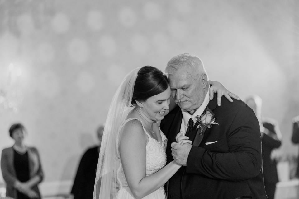 close up black and white photo of father and bride during their traditional dance