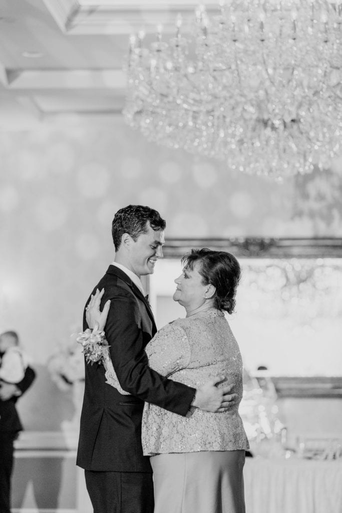 close up black and white photo of groom dancing with mother while wedding guests look on