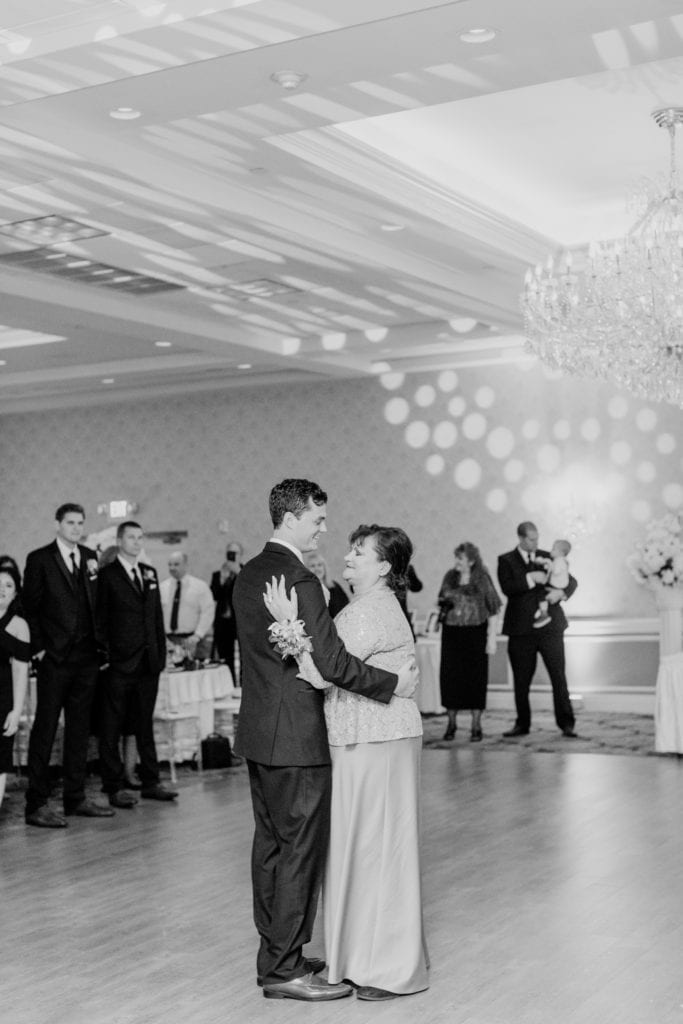 black and white photo of groom dancing with mother while wedding guests look on