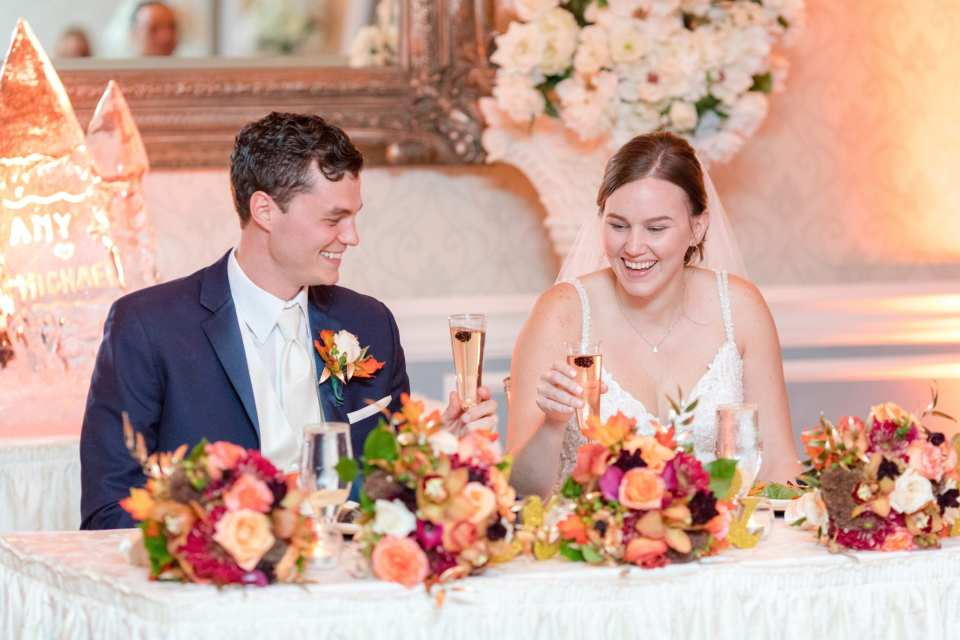 bride and groom sitting at sweet heart table that is covered with bridal party bouquets of fall colored flowers have a champagne toast