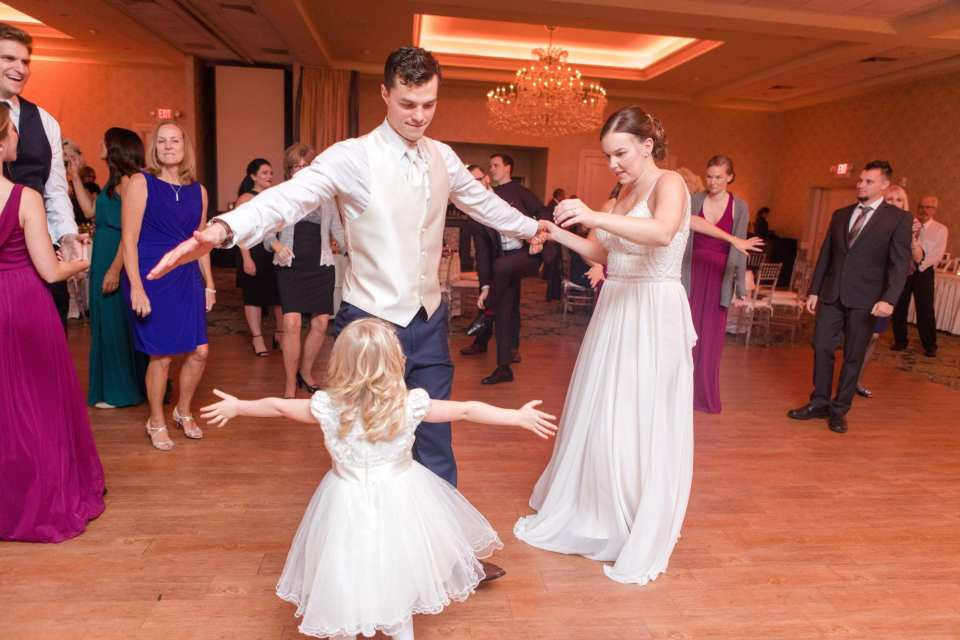 bride and groom dance with flower girl during reception