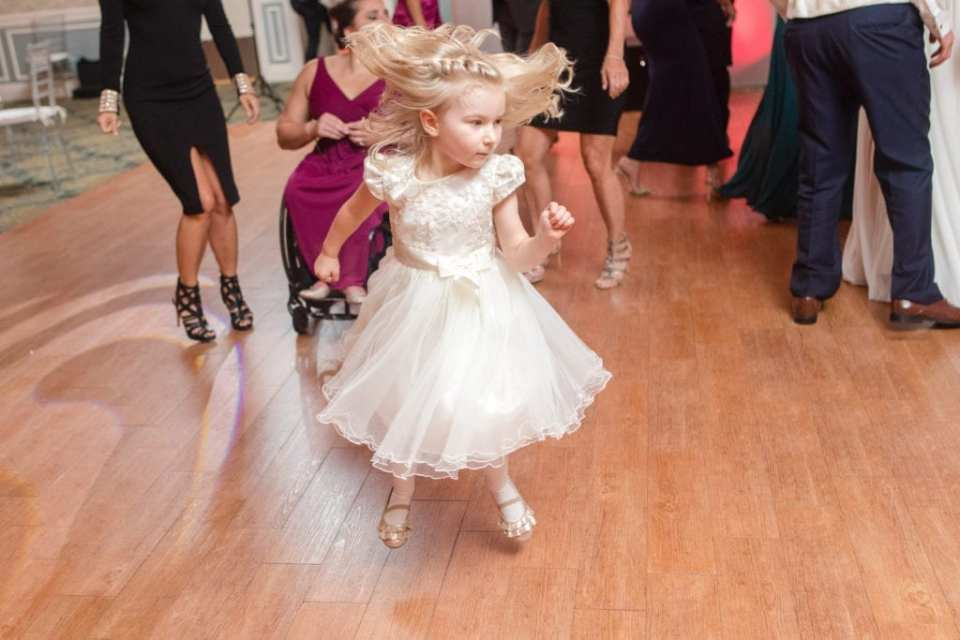 action photo of little blonde flower girl in off white dress dancing during reception