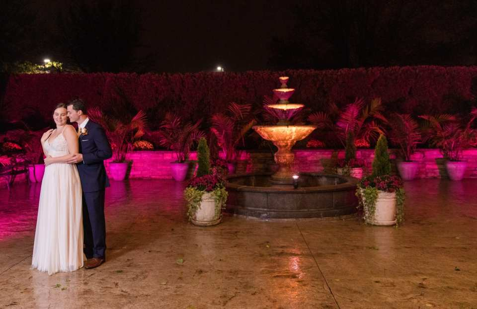 bride and groom portrait outdoors on patio with large fountain and many plants, with pink lighted hue