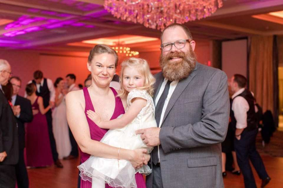 a member of the bridal party in a raspberry colored gown poses with a man and a young girl in a white dress during the reception