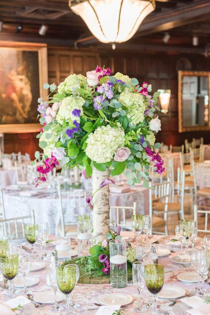 shot of tall table arrangement with birch wood stalk topped with greenery, lavender and cream roses, pale green hydrangeas, fuschia orchids