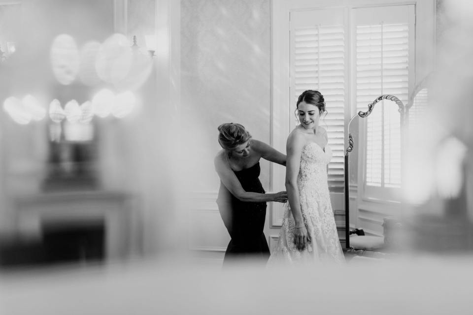 black and white photo of bride being helped into her gown by her mother in front of a mirror