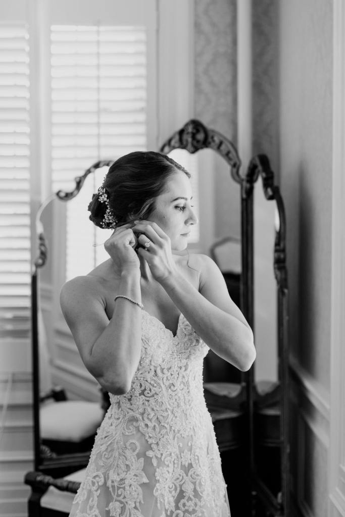 black and white photo of bride putting on her earring while gazing out the window