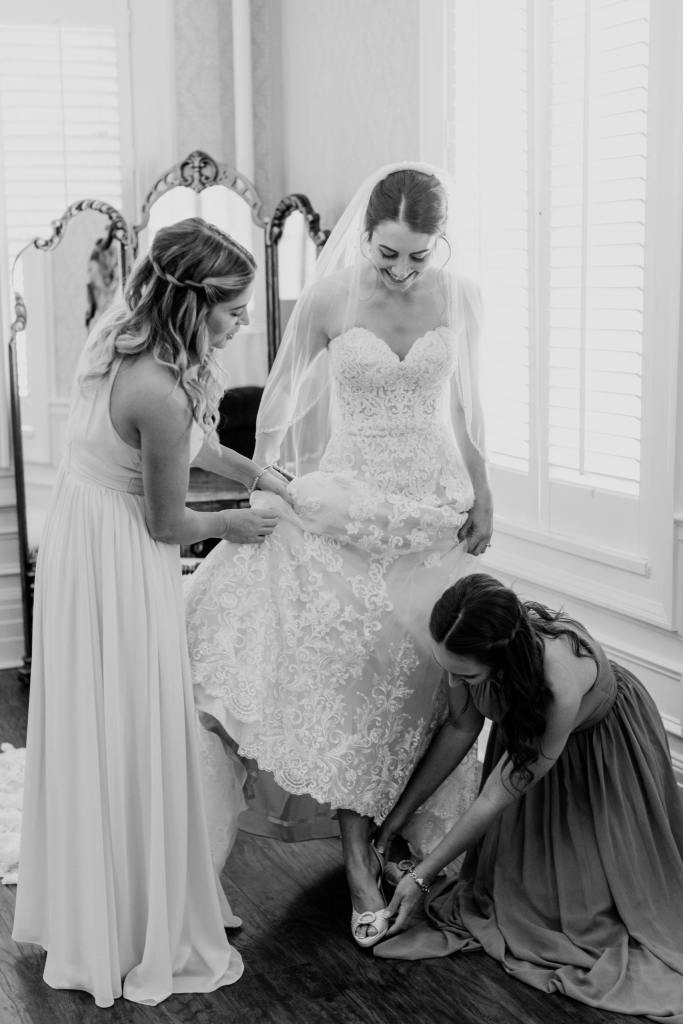 black and white photo of bride being helped into her shoes by members of her bridal party
