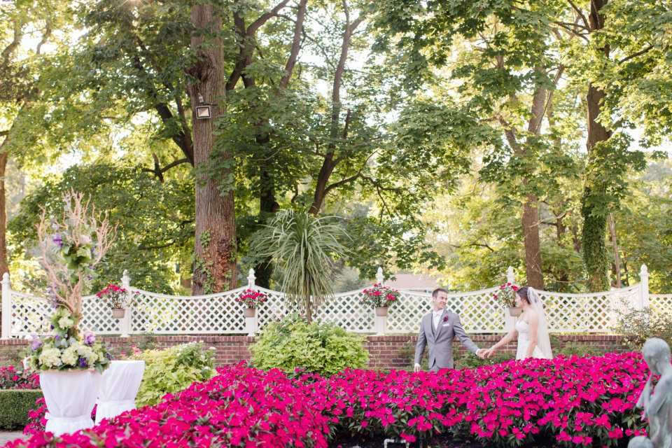 Bride and groom strolling through the lush gardens of Shadowbrook at Shrewsbury