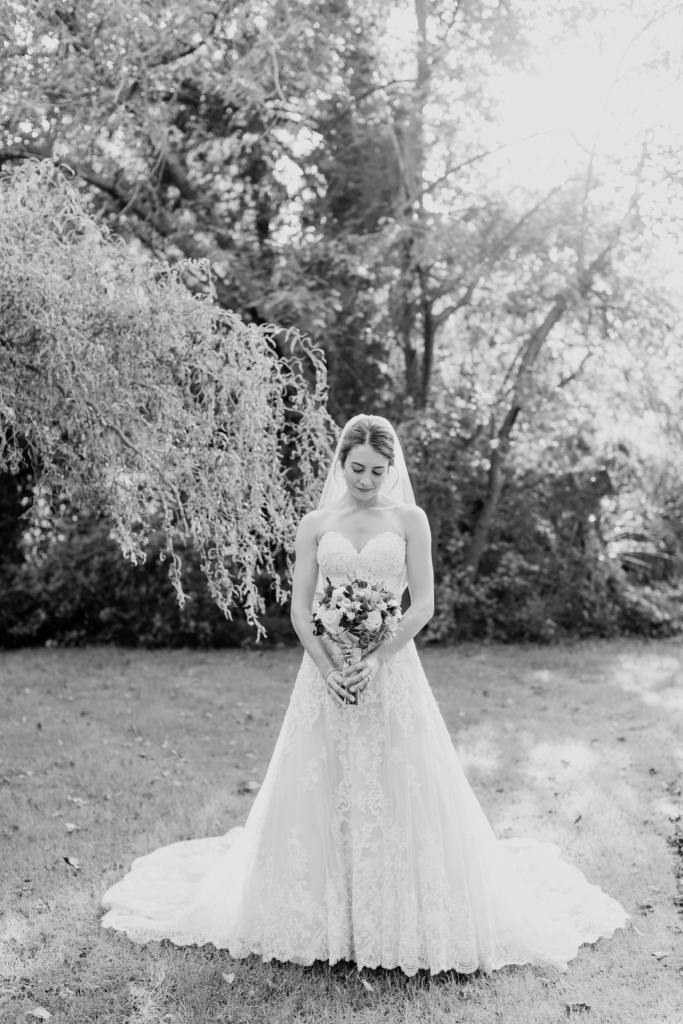 black and white full length bridal portrait surrounded by trees