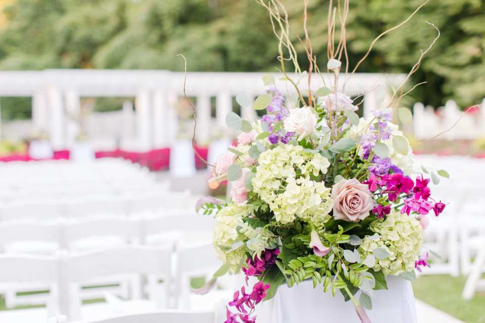 floral arrangement at the end of the outdoor ceremony aisle comprised of hydrangeas, light pink roses, branches, various orchids